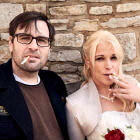 Das Hochzeitspaar an einer sandfarbenen Steinmauer mit Zigaretten im Mund schaut direkt in die Kamera - Schloss Schöningen © Hochzeitsfotograf www.hochzeitsverliebt.de