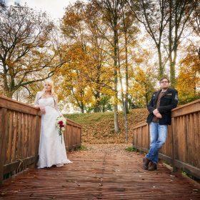 In Herbstfarben steht sich das Hochzeitspaar an einer braunen Holzbrücke gegenüber und sieht in Ferne - Schloss Schöningen © Hochzeitsfotograf www.hochzeitsverliebt.de