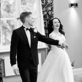 Der Bräutigam führt seine lachende Braut schwungvoll durch den Raum - Schlösschen Bad Nenndorf © Hochzeitsfotograf www.hochzeitsverliebt.de