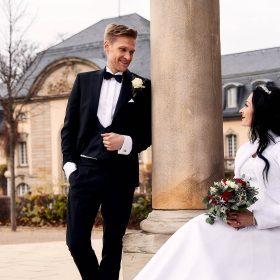 Bräutigam lehnt an der Säule und schaut auf seine sitzende Braut - Kurpark Bad Nenndorf © Hochzeitsfotograf www.hochzeitsverliebt.de