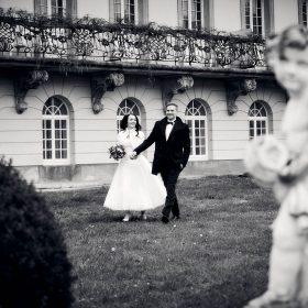 Schwarzweissbild vom Brautpaar, das vor dem Gebäude mit Balkon und vielen Fenstern über den Rasen spaziert - Kurpark Bad Nenndorf © Hochzeitsfotograf www.hochzeitsverliebt.de