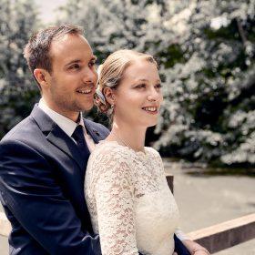 Bräutigam steht hinter seiner Braut und umarmt sie in der Natur am Steg - Junkerhof Wittingen © Hochzeitsfotograf www.hochzeitsverliebt.de
