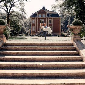 Der Bräutigam trägt seine Braut im Grünen auf Händen und läuft auf die helle Steintreppe zu - Schloss Eldingen © Hochzeitsfotograf www.hochzeitsverliebt.de