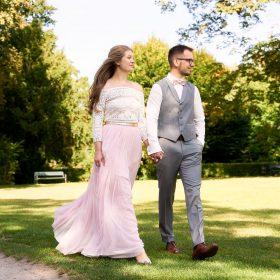 Braut und Bräutigam gehen Hand in Hand bei Sonnenschein über den Rasen - Kloster Wienhausen © Hochzeitsfotograf www.hochzeitsverliebt.de
