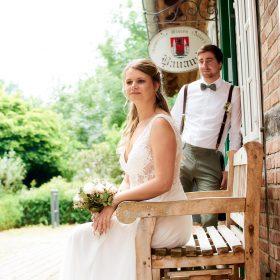 Sitzende Braut auf der Holzbank am roten Fachwerkhaus und grün mit Bräutigam im Hintergrund - Standesamt Winsen Aller © Hochzeitsfotograf www.hochzeitsverliebt.de