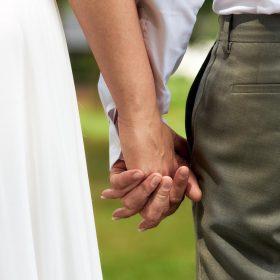 Detail vom Brautpaar im Grünen mit weissem Kleid und graugrüner Hose, das sich an den Händen hält - Kirchengarten Winsen Aller © Hochzeitsfotograf www.hochzeitsverliebt.de