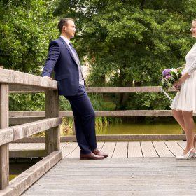 Das Brautpaar steht sich am Holzsteg am Geländer gegenüber und hat das Wasser mit Bäumen im Hintergrund - Junkerhof Wittingen © Hochzeitsfotograf www.hochzeitsverliebt.de