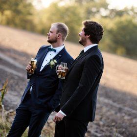 Zwei männliche Hochzeitsgäste stehen kurz vor dem Feld mit einem Glas Bier in den Händen - Hof Wietfeldt Bennebostel © Hochzeitsfotograf www.hochzeitsverliebt.de