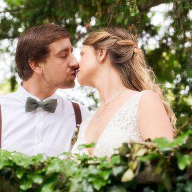 Das Brautpaar gibt sich an der mit Efeu bewachsenen Mauer einen Kuss - Kirchengarten Winsen Aller © Hochzeitsfotograf www.hochzeitsverliebt.de