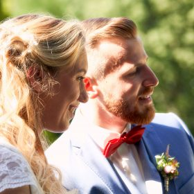Porträt im Seitenprofil vom Brautpaar in weiss und helllblau mit roter Fliege im Grünen - Schloss Eldingen © Hochzeitsfotograf www.hochzeitsverliebt.de