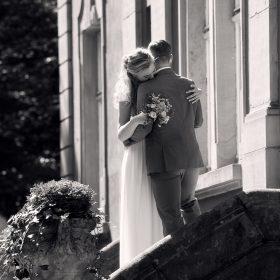 Schwarzweissbild vom Brautpaar am Schlosseingang auf der Treppe, dass sich umarmt - Schloss Eldingen © Hochzeitsfotograf www.hochzeitsverliebt.de