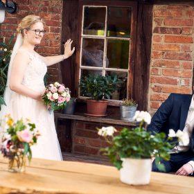 Die Braut in weiss steht am Fachwerk und schaut zu ihrem davor sitzenden Bräutigam - Hof Wietfeldt Bennebostel © Hochzeitsfotograf www.hochzeitsverliebt.de