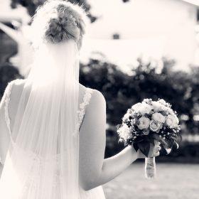 Braut als Schwarzweissaufnahme mit weissem Schleier wird von Sonnenstrahlen umgeben und hält ihren Strauß hoch - Hof Wietfeldt Bennebostel © Hochzeitsfotograf www.hochzeitsverliebt.de