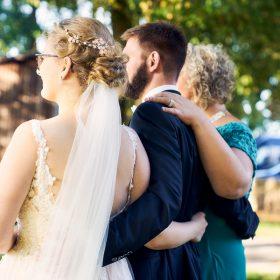 Schräge Perspektive von Braut und Bräutigam in Umarmung mit türkis gekleideter Brautmutter - Hof Wietfeldt Bennebostel © Hochzeitsfotograf www.hochzeitsverliebt.de