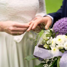 Ringwechsel vom Brautpaar im Grünen mit einem Brautstrauß in creme und violett - Junkerhof Wittingen © Hochzeitsfotograf www.hochzeitsverliebt.de