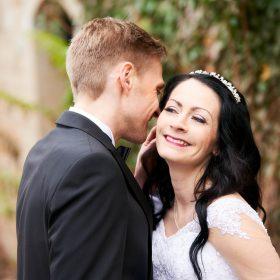 Bräutigam flüstert seiner Braut vor unscharfer Steinfassade liebevoll etwas zu - Kurpark Bad Nenndorf © Hochzeitsfotograf www.hochzeitsverliebt.de