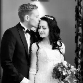 Das Hochzeitspaar in schwarzweiss steht am Fenster und der Mann küsst seine Frau auf die Stirn - Schlösschen Bad Nenndorf © Hochzeitsfotograf www.hochzeitsverliebt.de