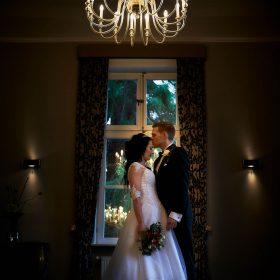 Braut und Bräutigam stehen im Abendlicht unterm strahlenden Kronleuchter im Raum - Schlösschen Bad Nenndorf © Hochzeitsfotograf www.hochzeitsverliebt.de