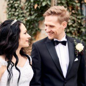 Das Brautpaar lächelt sich an am Steinhaus mit Efeuranken - Kurpark Bad Nenndorf © Hochzeitsfotograf www.hochzeitsverliebt.de