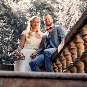 Das Brautpaar aus der Perspektive von unten auf der Steinbalustrade - Schloss Eldingen © Hochzeitsfotograf www.hochzeitsverliebt.de