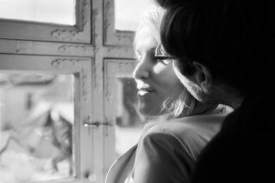 Schwarzweissbild vom Hochzeitspaar am Fenster, bei dem der Bräutigam seine Frau auf die Wange küsst - Schloss Schöningen © Hochzeitsfotograf www.hochzeitsverliebt.de