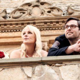 Braut und Bräutigam sehen vom oberen Schlosseingang in die Ferne und lehnen am hellen Steingeländer  - Schloss Schöningen © Hochzeitsfotograf www.hochzeitsverliebt.de