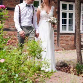 Das Hochzeitspaar geht am Fachwerkhaus Rosenweg entlang - Standesamt Winsen Aller © Hochzeitsfotograf www.hochzeitsverliebt.de