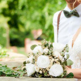 Detail vom Brautpaar im Grünen an Steinmauer mit Efeu und Brautstrauß aus weissen Rosen - Standesamt Winsen Aller © Hochzeitsfotograf www.hochzeitsverliebt.de