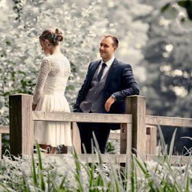 Bräutigam schaut zu seiner Braut in weiss, die am Geländer der Holzbrücke lehnt - Junkerhof Wittingen © Hochzeitsfotograf www.hochzeitsverliebt.de