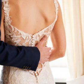 Bräutigam umarmt seine Braut im Spitzenkleid mit Rückenausschnitt - Celle Althoff Hotel Fürstenhof © Hochzeitsfotograf www.hochzeitsverliebt.de