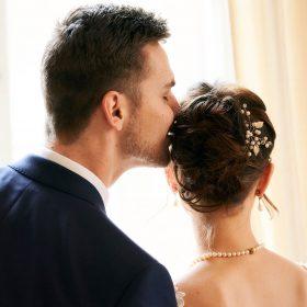 Bräutigam gibt seiner Braut am Fenster einen Kuss auf die Haare - Celle Althoff Hotel Fürstenhof © Hochzeitsfotograf www.hochzeitsverliebt.de
