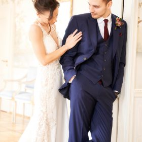 Braut steht beim lässig stehenden Bräutigam am Türrahmen und schaut auf seinen Anzug - Celle Althoff Hotel Fürstenhof © Hochzeitsfotograf www.hochzeitsverliebt.de