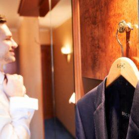 Sakko vom Bräutigam hängt am Holzschrank auf dem hellen Holzbügel und der Bräutigam im weissen Hemd bindet sich lächelnd die Krawatte - Celle Ringhotel Celler Tor © Hochzeitsfotograf www.hochzeitsverliebt.de