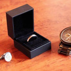 Ehering in geöffneter, schwarzer Schatulle liegt auf dem Holztisch mit der braunen Uhr und silbernen Manschettenknöpfen - Celle Ringhotel Celler Tor © Hochzeitsfotograf www.hochzeitsverliebt.de