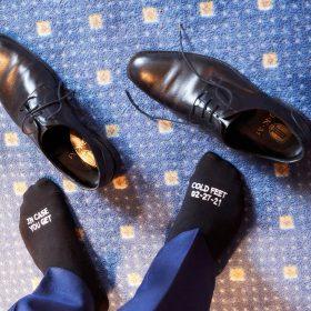 Schwarze Schuhe mit Füssen vom Bräutigam in schwarzen Socken auf blau gemustertem Teppich aus der Vogelperspektive - Celle Ringhotel Celler Tor © Hochzeitsfotograf www.hochzeitsverliebt.de