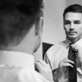Schwarzweissaufnahme vom Spiegelbild des Bräutigams während seiner Krawattenbindung - Celle Ringhotel Celler Tor © Hochzeitsfotograf www.hochzeitsverliebt.de