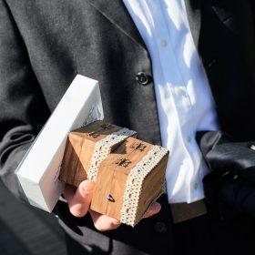 Detail vom Mann mit weissem Hemd und anthrazit Sakko sowie zwei hellbraunen Holzschatullen mit Stickerei in der Hand - Hof Wietfeldt Bennebostel © Hochzeitsfotograf www.hochzeitsverliebt.de