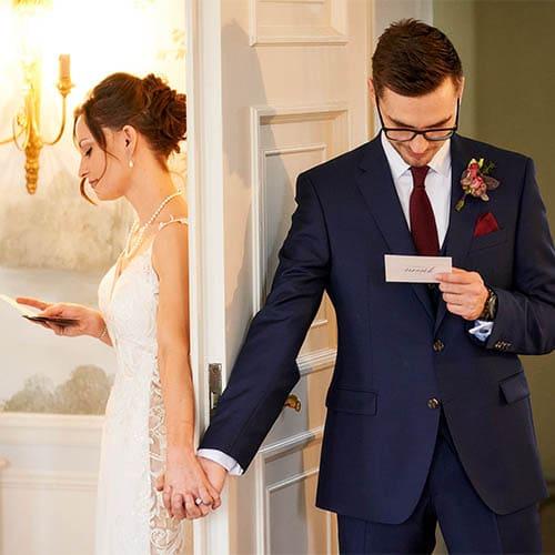 Brautpaar steht zwischen der weissen Tür und tauscht händchenhaltend Liebesbriefe aus - Celle Althoff Hotel Fürstenhof © Hochzeitsfotograf www.hochzeitsverliebt.de