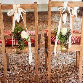 Zwei Holzstühle für Braut und Bräutigam mit roten Kissen und Schleifen in creme an der Lehne und hängenden, gefüllten Blumengläsern - Hof Wietfeldt Bennebostel © Hochzeitsfotograf www.hochzeitsverliebt.de
