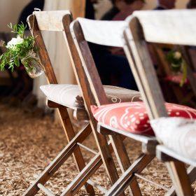 Stuhlreihe aus Holzklappstühlen mit Kissen in Scheune - Hof Wietfeldt Bennebostel © Hochzeitsfotograf www.hochzeitsverliebt.de