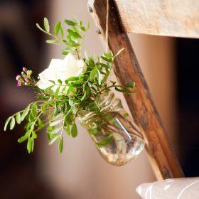 Nahaufnahme vom hängenden Blumengesteck im Glas am Holzstuhl - Hof Wietfeldt Bennebostel © Hochzeitsfotograf www.hochzeitsverliebt.de