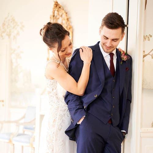 Die Braut in weiss schmiegt sich an den in blau gekleideten Bräutigam, der lässig im Türrahmen anlehnt - Celle Althoff Hotel Fürstenhof © Hochzeitsfotograf www.hochzeitsverliebt.de
