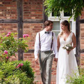 Spaziergang des Brautpaares am Rosenweg mit Fachwerk im Hintergrund - Standesamt Winsen Aller © Hochzeitsfotograf www.hochzeitsverliebt.de