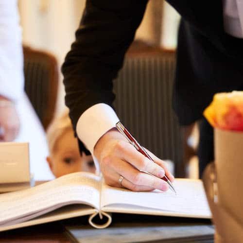 Die Hand vom Bräutigam mit rotem Stift unterschreibt das Eheversprechen - Schlösschen Bad Nenndorf bei Hannover © Hochzeitsfotograf www.hochzeitsverliebt.de