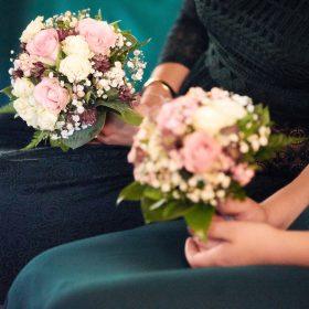 Ausschnitt von in grün und blau gekleideten Frauen mit Röcken und Blumensträußen in Pastelltönen- Hof Wietfeldt Bennebostel © Hochzeitsfotograf www.hochzeitsverliebt.de