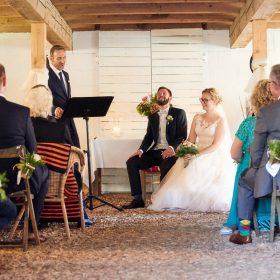Brautpaar sitzt vorne lachend beim Trauredner und wird von der Hochzeitsgesellschaft beobachtet - Hof Wietfeldt Bennebostel © Hochzeitsfotograf www.hochzeitsverliebt.de