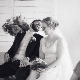 Schwarzweissbild vom herzlich lachenden Brautpaar, das sich sitzend an den Händen hält - Hof Wietfeldt Bennebostel © Hochzeitsfotograf www.hochzeitsverliebt.de
