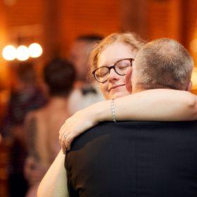 Die Braut umarmt ihren Vater mit Gästen im Hintergrund der Hochzeitslocation - Hof Wietfeldt Bennebostel © Hochzeitsfotograf www.hochzeitsverliebt.de