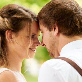 Porträt vom Hochzeitspaar in der Natur, dass sich Stirn an Stirn anlächelt - Kirchengarten Winsen Aller © Hochzeitsfotograf www.hochzeitsverliebt.de