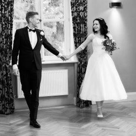 Brautpaar schreitet Hände haltend durch den hellen Raum mit großen Fenstern, hier als Schwarzweissbild - Schlösschen Bad Nenndorf © Hochzeitsfotograf www.hochzeitsverliebt.de